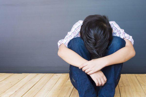 menino sentado no chão triste