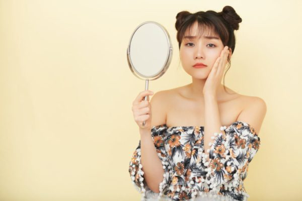 mulher se olhando no espelho triste
