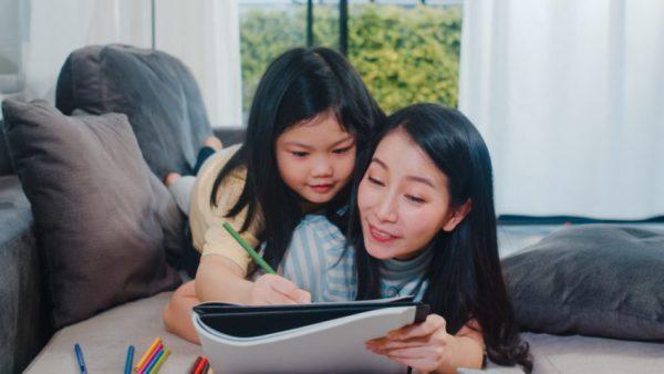 Mãe e criança com caderno estudando juntas