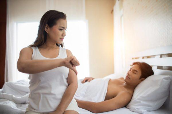 mulher fazendo sinal negativo para esposo na cama
