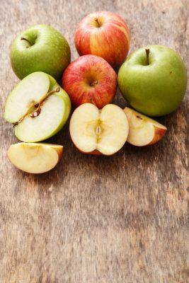maçãs inteiras e maçãs partidas ao meio em cima de uma mesa