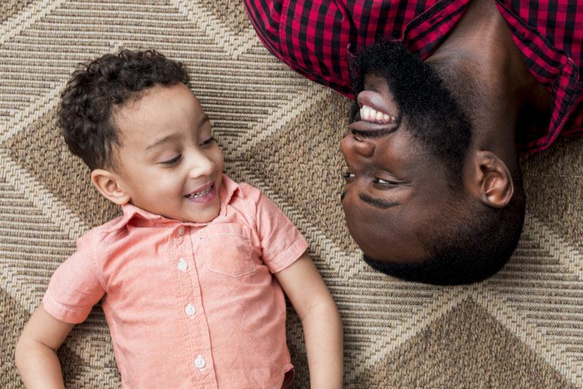Pai e filho deitados no tapete se olhando felizes
