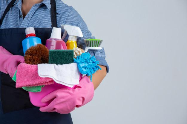 Mulher segurando balde com produtos de limpeza para higienizar a casa