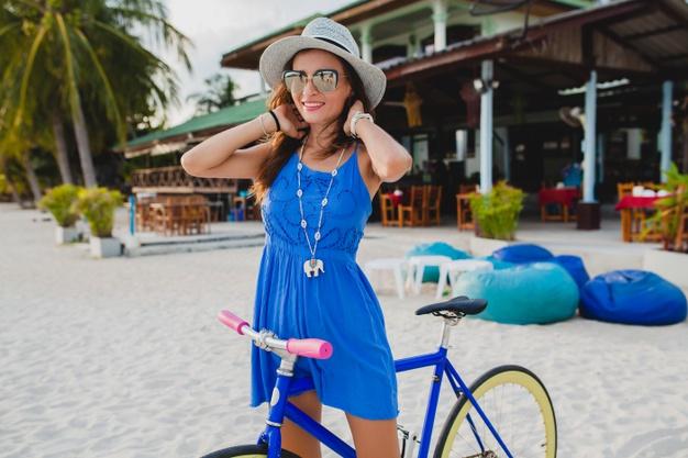 Mulher de vestido azul na bicicleta azul