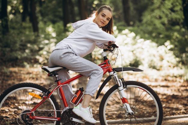 Mulher gravida parada na bicicleta