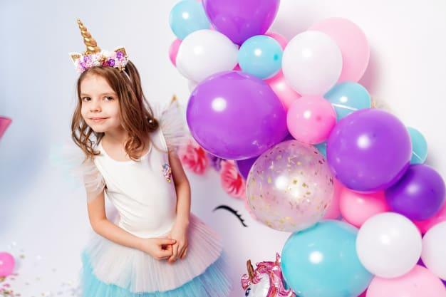 Menina com roupa de festa e bolas