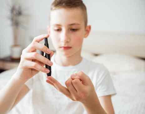 crianças fazendo teste de glicose no dedo