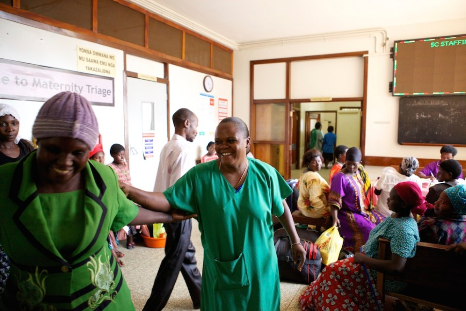 A midwife smiling after interacting with a patient in the hospital, Uganda.