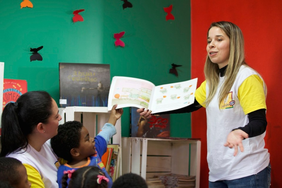 A C&A volunteer reading to a group of school children