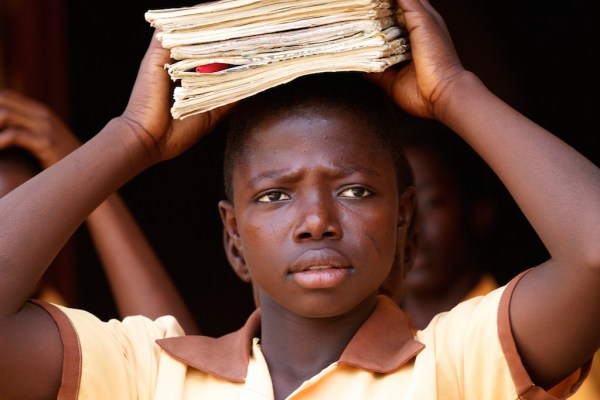 A school girl carrying book on her head in Ghana.