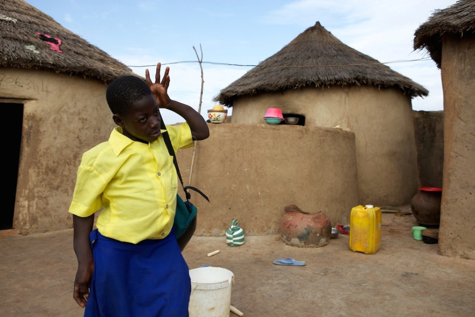 School girl walking leaving home in the morning with her school bag. Behind her are the mud huts of her family home in Ghana