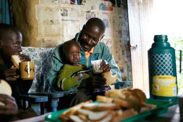 This photo is taken inside a mut hut in Kenya. A man smiling as he looks at his son sitting on his lap.
