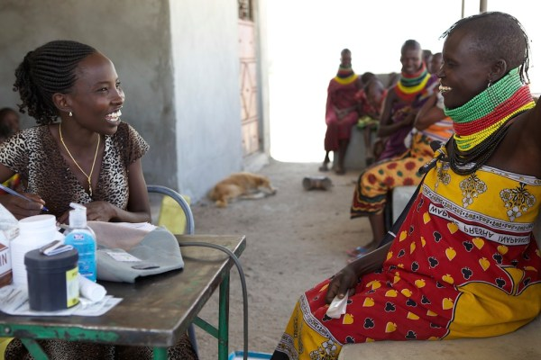 A patient and nurse smiling at each other at an outreach health post in Turkana in Kenya.