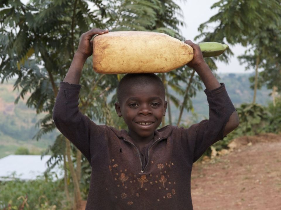 A boy carrying a container of water on his head, Rwanda.