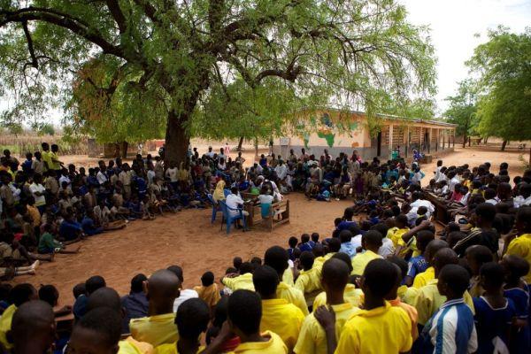 School children watching a play under a tree in northern Ghana, Africa