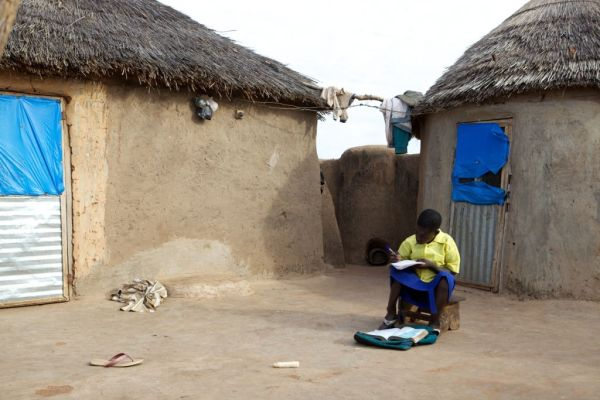 school girl doing her homework in the compound of her home in northern Ghana, Africa