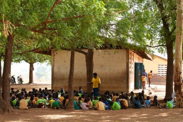 Children learning under a tree in Ghana, Africa