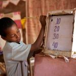 young boy at school using a board to do maths
