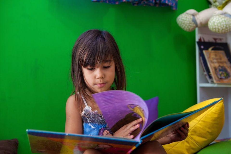 a young girl reading a big book