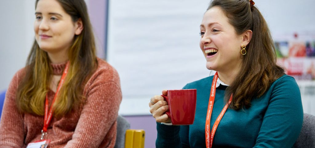 Two women in a meeting, drinking tea, engaged.
