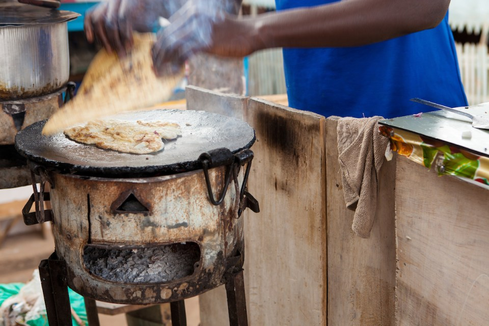 a man cooking a rolex- a type of japati with egg- over a wood burning oven in Uganda.