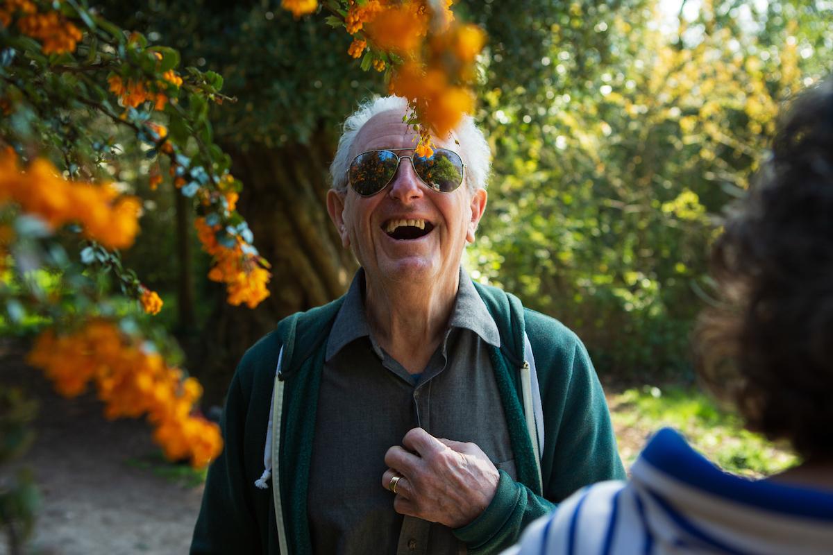 older man laughs amongst autumnal coloured trees