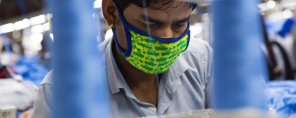 A man working on a sewing machine in an Indian organic cotton factory.