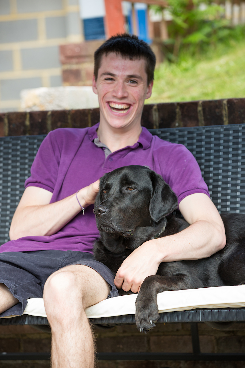 Young man sitting with his black labrador Dogs for Good assistance dog