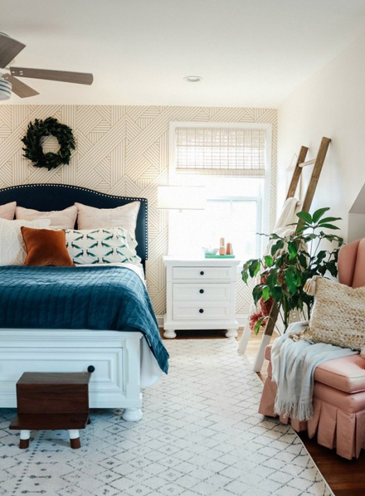 Dormitorio de matrimonio alegre y bonito con textiles azules y papel pintado