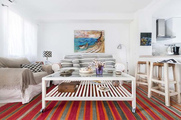 Çok renkli bir halıya sahip küçük bir oturma odası