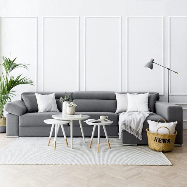 Beyaz ve gri yastıkları birleştiren gri bir kanepe