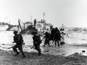 Chaotic scenes as Allied troops leave their landing crafts to face the German machine guns. The film intercuts shots of Tom's body being removed from his craft with archive footage of dead and wounded soldiers being returned to Britain.