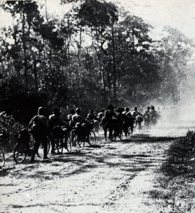 Japanese soldiers on bicycles move down a jungle road in 1942