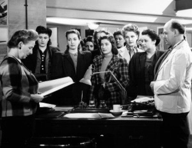 CELIA (PATRICIA ROC) STANDS IN THE MIDDLE OF HER FELLOW WORKERS AS A MEETING TAKES PLACE.