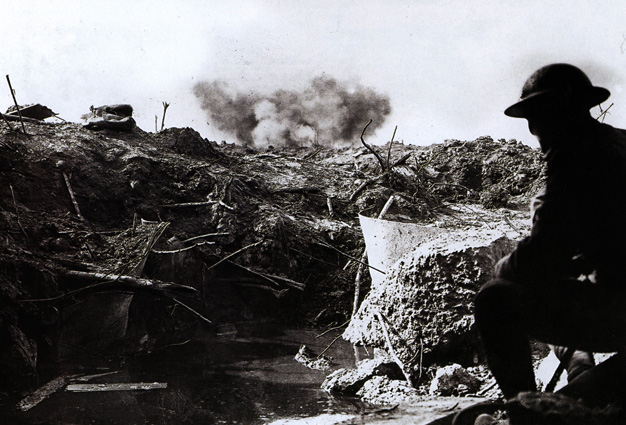 A British soldier lies low in a captured German emplacement.