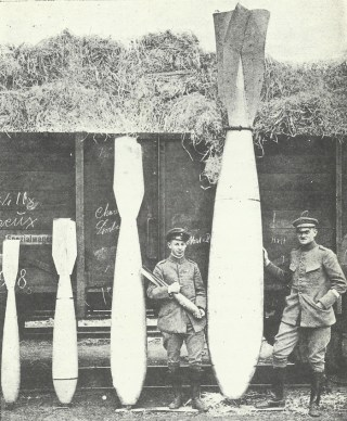 The range of bombs carried by Gothas and Giants. From left to right are 50kg, 100kg, 300kg, and 1,000kg bombs, with the man in the centre holding a 12.5kg bomb.