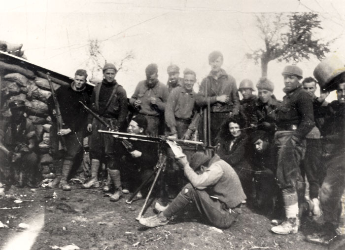 Black and white photograph of Orwell, standing sixth from the left with a rifle slung over his arm, on the Aragon front of the Spanish Civil War, 1937.