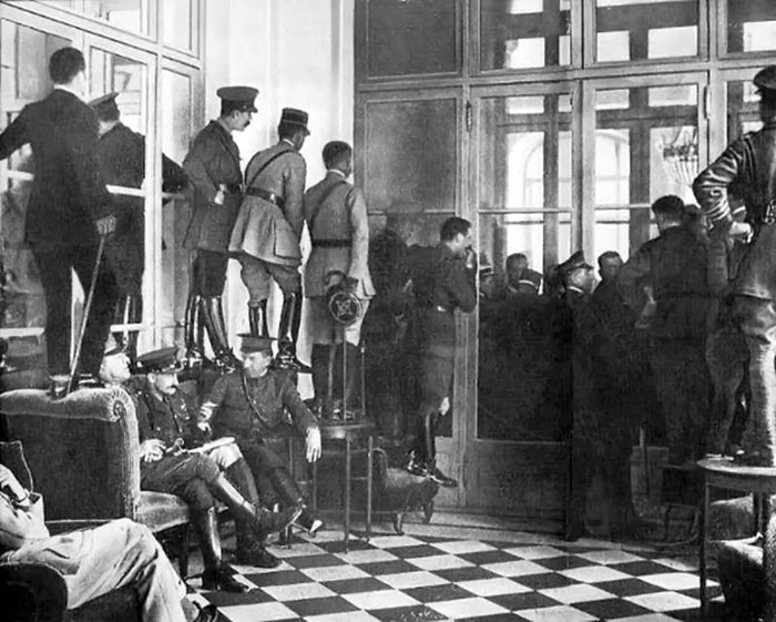 Black and white photograph showing a room of people, many stood on tables and chairs, peering through glass doors trying to catch a glimpse of the Treaty of Versailles being signed.