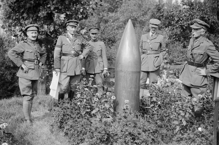Black and white photograph of William Beach Thomas and soldiers examining a dud shell on the Western Front.