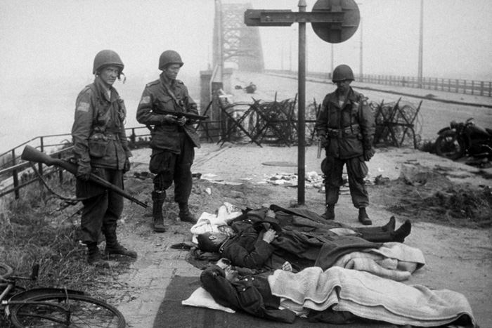 Paratroopers from the US 82nd Airborne Division, possibly from the 2nd Battalion 505 Parachute Infantry Regiment, stand guard over wounded German prisoners at the south end of the Nijmegen road bridge.
