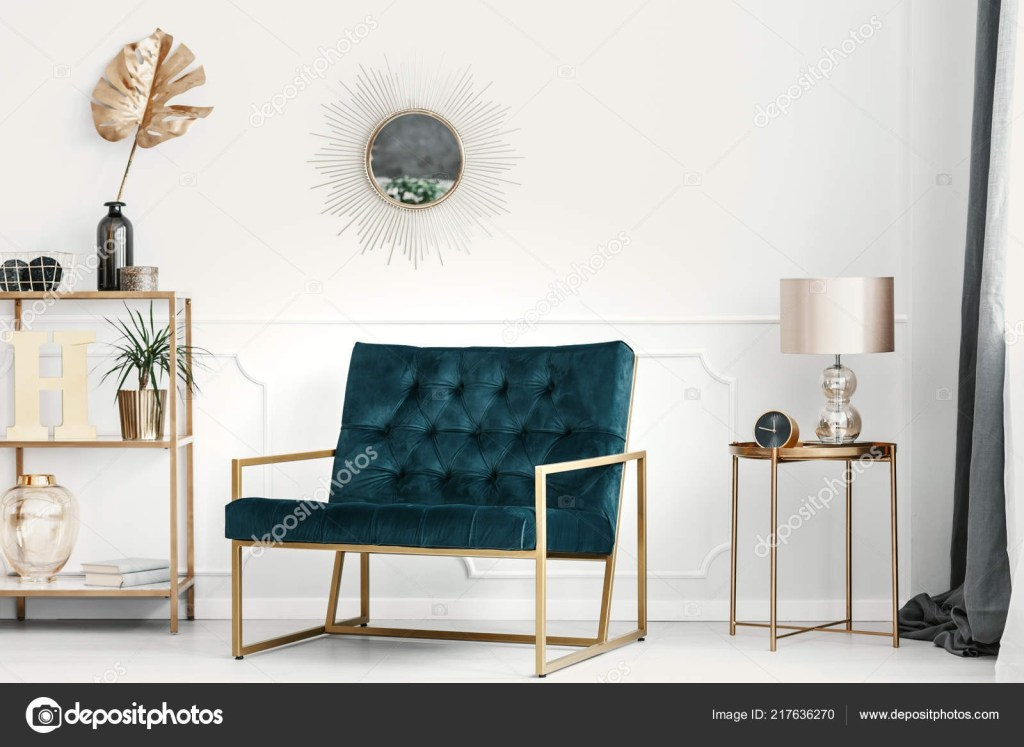 golden decorations and furniture in an expensive living room interior with an emerald green sofa a white wall with molding 217636270