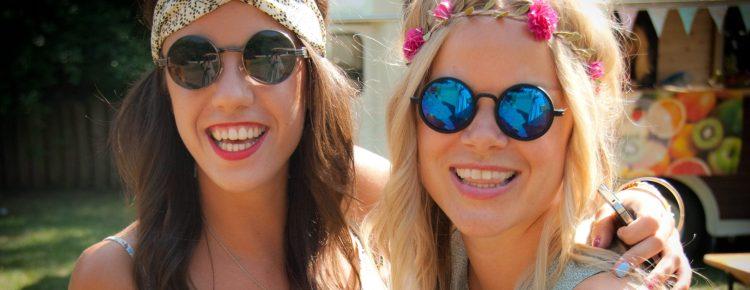To damer kledd ut som hippier på syttitallsfest.