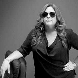 Jenni Halamuda with sunglasses leaning on a chair