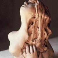 Opposition entre les formes lisses et les formes en désordre. C'est une femme qui remet en place sa chevelure en désordre, ou qui essaie de retenir son cœur déchiré
