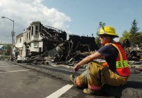 """Milo firefighter Wayne Russell takes in the destruction of the town's Main Street, which was largely wiped out by an early morning blaze on Sunday. Russell stated the firefighters had expected the close, old wooden building to someday be the scene of a fire, but their premonitions proved futile when the scenario actually occurred. """"Every fire is different,"""" says Russell, who spent most of Sunday and Monday at the scene."""