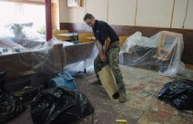 George Quinn of Penobscot Cleaning Services removes the flooring from Milo House of Pizza on Wednesday, September 17, 2008. Although the restaurant was the only Main Street structure to survive Sunday's deliberately set fire, the building sustained heavy smoke and water damage.