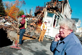 Sandra Haley, lifelong resident of Milo and owner of the Milo Flower Shop, watches as crews tear down the burnt out remains of her business.