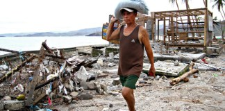 A resident carrying relief goods walks past houses damaged by Typhoon Pablo at Ugpason Beach, Barangay San Roque, in the town of Lingig, Surigao del Sur on Christmas Day. MindaNews photo by Erwin Mascarinas