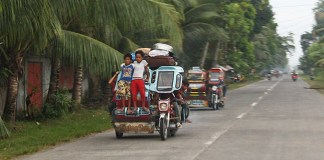 Young boys stand on the 'bumper' of a speeding tricycle, unmindful of the danger on Tuesday, September 24 in Barangay Tumbras, Midsayap town, North Cotabato Province. These boys are heading home after spending a night at the evacuation center when the Bangsamoro Islamic Freedom Fighters attacked several barangays in Midsayap on Monday. MindaNews Photo by Ruby Thursday More