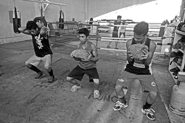 Because they lack equipment, 17-year-old Salvador Salva (center) and other boxers use rocks for their weight training.